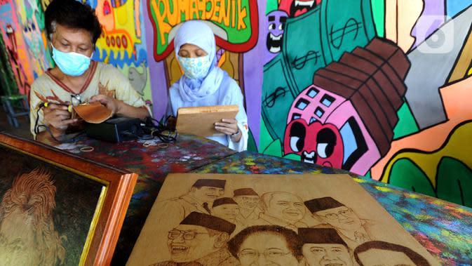Arfan (55) seniman pelukis bakar atau pyrography bersama istri menyelesaikan karya seni lukis bakar di atas media kayu dan kulit di galeri Rumah Oenik, Kampung Ragamukti, Tajur Halang, Bogor, Senin (28/9/2020). (Merdeka.com/Arie Basuki)