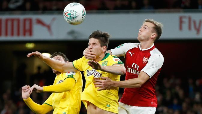 Pemain Arsenal, Rob Holding berusaha menyundul bola dari pemain Norwich City, Timm Klose pada lanjutan Piala Liga Inggris di Emirates Stadium, Rabu (25/10). Edward Nketiah memborong gol Arsenal saat mengalahkan Norwich City 2-1. (AP/Alastair Grant)