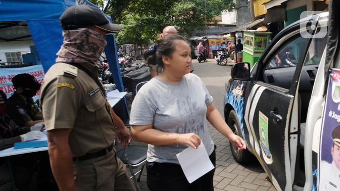 Seorang perempuan yang tidak mengenakan masker bersiap menaiki mobil Satpol PP di Tangerang, Kamis (14/5/2020). Pemkot Tangerang melakukan tindakan bagi pelanggar PSBB dengan membawa mereka ke kantor Kecamatan Karawaci Baru untuk dilakukan rapid test Covid-19. (Liputan6.com/Angga Yuniar)