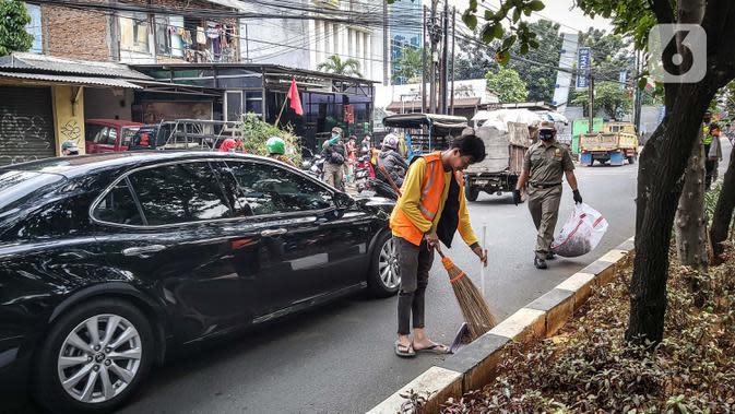 Warga menyapu jalan saat terkena razia masker di kawasan Karang Tengah Raya, Lebak Bulus, Jakarta, Senin (14/9/2020). Penertiban terkait pelaksanaan PSBB Jakarta kembali dan memutus rantai penyebaran COVID 19. (Liputan6.com/Faizal Fanani)