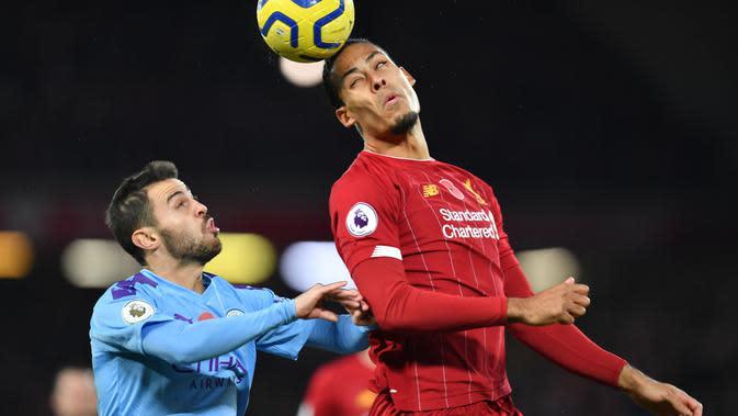 Bek Liverpool, Virgil Van Dijk, menyundul bola saat melawan Manchester City pada laga Premier League di Stadion Anfield, Liverpool, Minggu (10/11). Liverpool menang 3-1 atas City. (AFP/Paul Ellis)