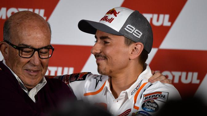 Pembalap Repsol Honda, Jorge Lorenzo (kanan) dan CEO Dorna, Carmelo Ezpelata, saat konferensi pers pengumuman sang pembalap pensiun jelang MotoGP Valencia, Kamis (14/11/2019). (AFP/Jose Jordan)