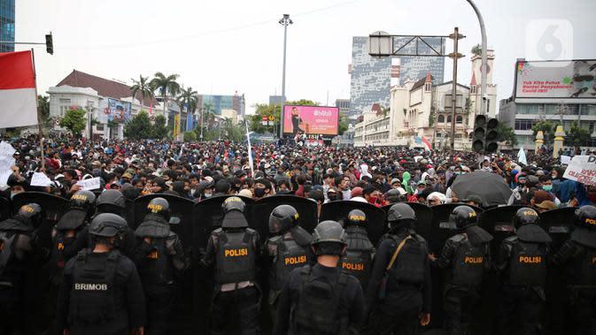 Polisi menjaga unjuk rasa menolak UU Cipta Kerja di kawasan Harmoni, Jakarta, Kamis (8/10/2020). UU Cipta Kerja yang disahkan beberapa waktu lalu memicu demonstasi sejumlah kalangan. (Liputan6.com/Faizal Fanani)