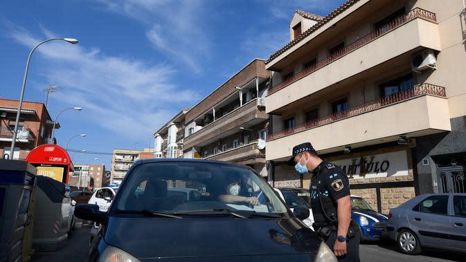 Seorang petugas polisi setempat memeriksa dokumen pengemudi di pos pemeriksaan lalu lintas untuk mengendalikan pergerakan orang-orang di kota Fuenlabrada yang tertutup sebagian, di wilayah Madrid (22/9/2020). Penguncian dilakukan akibat infeksi virus melonjak. (AFP/Oscar Del Pozo)