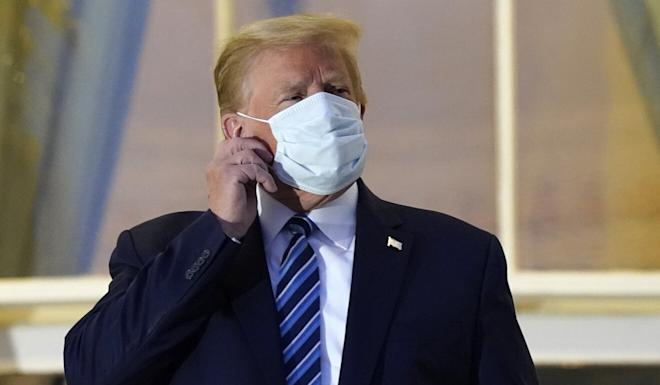 US President Donald Trump removes his mask after he returned to the White House from Walter Reed National Military Medical Center on October 5. Photo: AP