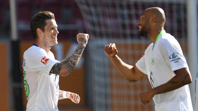Pemain Wolfsburg Daniel Ginczek dan John Brooks merayakan gol yang dicetak ke gawang FC Augsburg pada laga Bundesliga di Augsburg, Sabtu (16/5/2020). Pandemi COVID-19 membuat pemain melakukan selebrasi jaga jarak. (AFP/Tobias Hase)