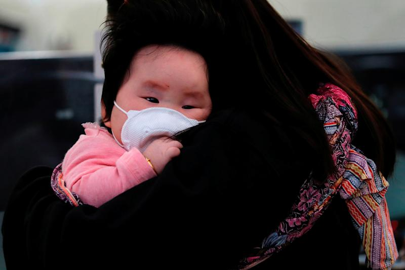 A child wears a mask to prevent an outbreak of a new coronavirus at the Hong Kong West Kowloon High Speed Train Station, in Hong Kong, China January 23, 2020. REUTERS/Tyrone Siu