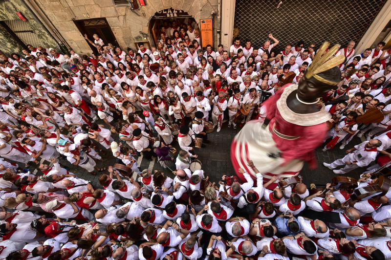 A giant member of San Fermin Comparse Parade takes part in a procession surrounded by people dressed in white and red clothes at the San Fermin Festival in Pamplona, northern Spain, Sunday, July 7, 2019. Revellers from around the world flock to Pamplona every year to take part in the eight days of the running of the bulls. (AP Photo/Alvaro Barrientos)