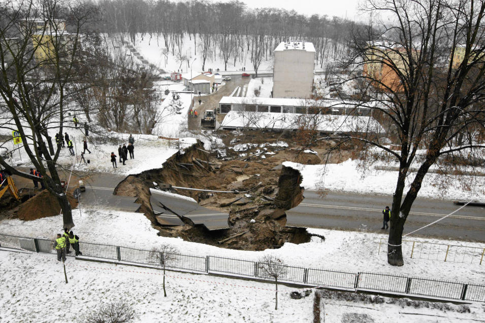 Onlookers examine the damage after a section of a road collapsed in Ostrowiec Swietokrzyski, southern Poland