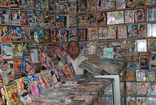 """In this photo taken on Feb. 19, 2013, an owner waits for customers at his DVD shop in Abbottabad, Pakistan. Pakistan stars in """"Zero Dark Thirty,"""" from early scenes at a detention site to the dramatic closing minutes as Navy SEALs assault the hideout of bin Laden. But the Academy Award-nominated film about the hunt for the al-Qaida leader has sparked a controversy here about its portrayal of the country, and it will likely not be shown on the local big screen anytime soon. Partly, the film taps into national discomfort that bin Laden was found to be living for years near Pakistan's equivalent. (AP Photo/Aqeel Ahmed)"""