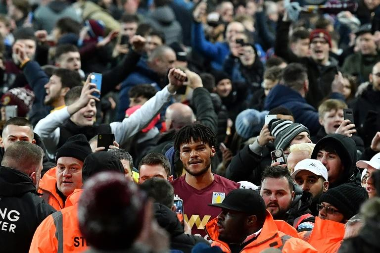 Aston Villa's defender Tyrone Mings is mobbed as fans poured onto the pitch after their 2-1 win over Leicester