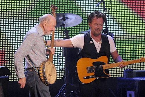 File-This Sept. 21, 2013, file photo shows Pete Seeger, left, being welcomed on stage by John Mellencamp during the Farm Aid 2013 concert at Saratoga Performing Arts Center in Saratoga Springs, N.Y. The American troubadour, folk singer and activist Seeger died Monday Jan. 27, 2014, at age 94. (AP Photo/Hans Pennink, File)