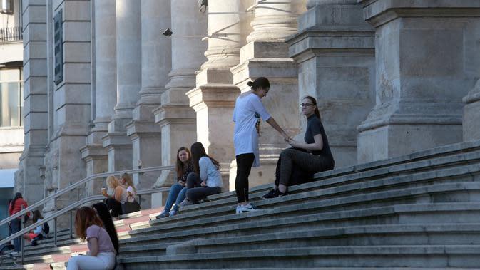 Warga tampak duduk di tangga halaman depan Museum Sejarah Nasional di Bucharest, Rumania, pada 7 Juni 2020. Setelah dua tahap penerapan langkah pelonggaran, warga Rumania kini menjalani