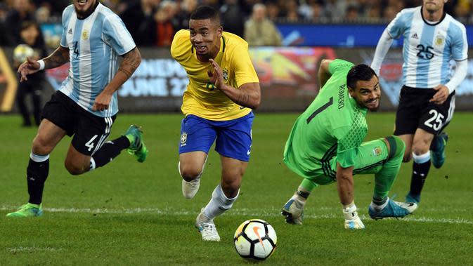 Penyerang Brasil, Gabriel Jesus berusaha mengejar bola usai melewati kiper Argentina, Sergio Romero saat pertandingan persahabatan di MCG di Melbourne (9/6). Argentina menang atas Brasil dengan skor 1-0. (AFP Photo/Saeed Khan)