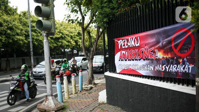 Pengendara motor melintas di dekat spanduk imbauan tolak anarkisme di Jakarta, Minggu (11/10/2020). Spanduk imbauan untuk tidak melakukan aksi anarkisme merebak di sejumlah kawasan di Jakarta pascaaksi unjuk rasa massa yang menolak pengesahan Omnibus Law UU Cipta Kerja. (Liputan6.com/Faizal Fanani)