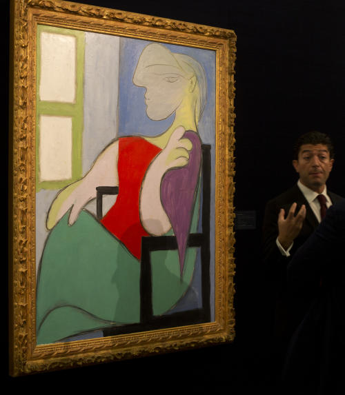 "FILE - In this Jan. 31, 2013 file photo, an expert from Sotheby's auction house gestures as he describes a 1932 painting by Pablo Picasso entitled ""Femme Assise Pres d'une Fenetre"" (Woman Sitting Near a Window), at Sotheby's auction house during a press preview in London. The painting fetched 28.6 million pounds ($44.9 million) at a London auction held Tuesday, Feb. 5, 2013. (AP Photo/Alastair Grant, File)"