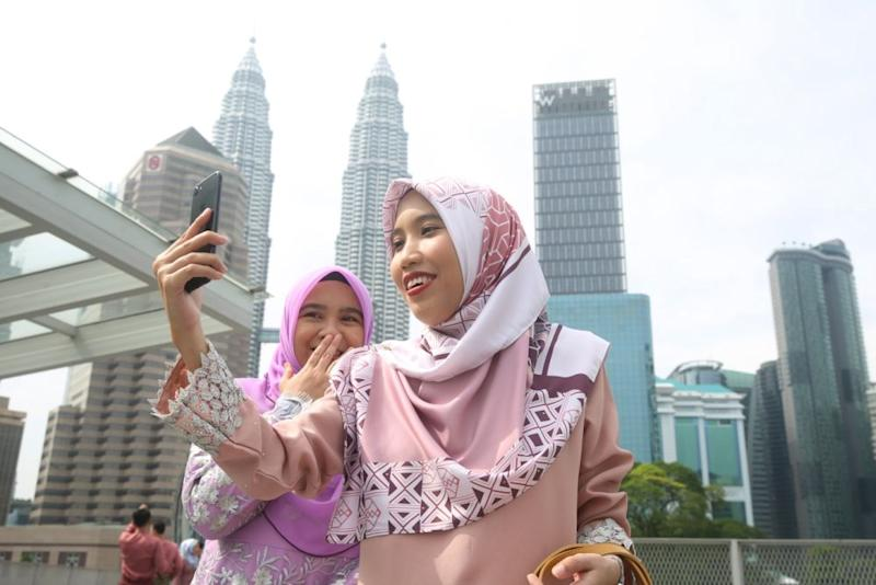 Members of the public pose for pictures at the Saloma Link Bridge in Kuala Lumpur on the first day of Syawal May 24, 2020. — Picture by Choo Choy May