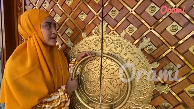 Inilah beberapa potret rumah ustaz Solmed dan April yang diambil dari tayangan video Orami Indonesia. April memperlihatkan pintu utama rumahnya dengan ukiran warna keemasan. (Youtube/Orami Indonesia)