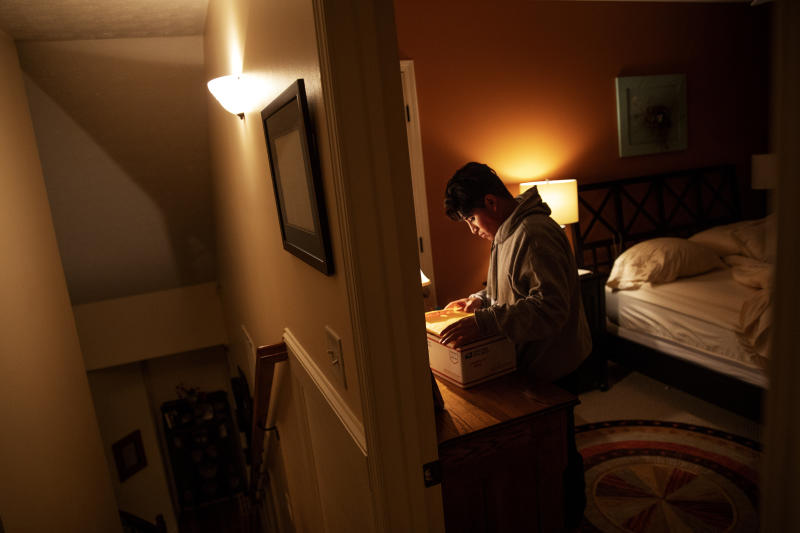 Andrea, 20, a transgender asylum seeker from Guatemala, sorts through documents as she settles in for the night at the home of a volunteer after her bond release from four months detained at the Stewart Detention Center, Tuesday, Nov. 12, 2019, in Columbus, Ga. Without any family in the area, Andrea would board a bus the next morning for the 23 hour bus ride to see her father in New York. (AP Photo/David Goldman)