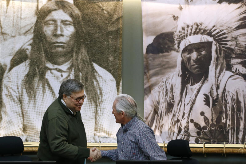Attorney General William Barr greets Leonard Gray, vice chairman of the Confederated Salish and Kootenai Tribes council, before speaking at a council meeting, Friday, Nov. 22, 2019, on the Flathead Reservation in Pablo, Mont. (AP Photo/Patrick Semansky)
