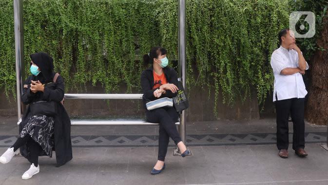 SOCIAL DISTANCING DI JAKARTA: Warga melakukan jaga jarak atau social distancing di kawasan Jalan MH Thamrin, Jakarta, Rabu (18/3/2020). Social distancing harus diterapkan kepada masyarakat yang masih melakukan aktivitas di luar untuk menghindari penyebaran COVID-19. (Liputan6.com/Angga Yuniar)