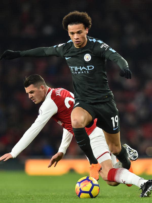 Gelandang Manchester City Leroy Sane berebut bola dengan pemain Arsenal, Granit Xhaka pada laga pekan ke-28 Premier League di Emirates Stadium, Jumat (2/3). Tampil di kandang lawan, Manchester City melibas Arsenal dengan skor 3-0. (Glyn KIRK/AFP)