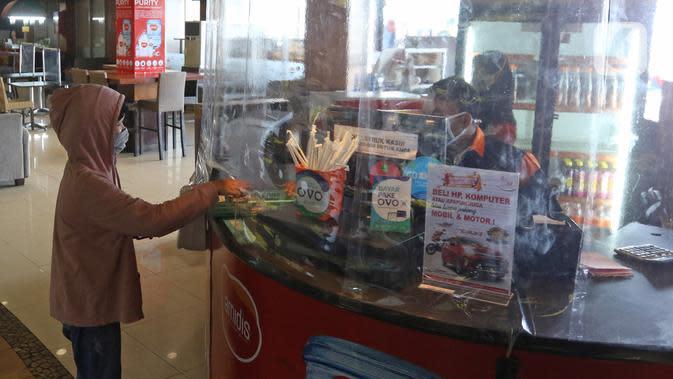 Pengunjung membayar di kasir yang dikasih pembatas plastik di salah satu restoran Mall Bekasi, Jawa Barat, Minggu (7/6/2020). Sejumlah tempat makan mulai menerapkan protokol kesehatan untuk pengunjung yang makan ditempat untuk mencegah penyebaran wabah COVID-19. (Liputan6.com/Herman Zakharia)
