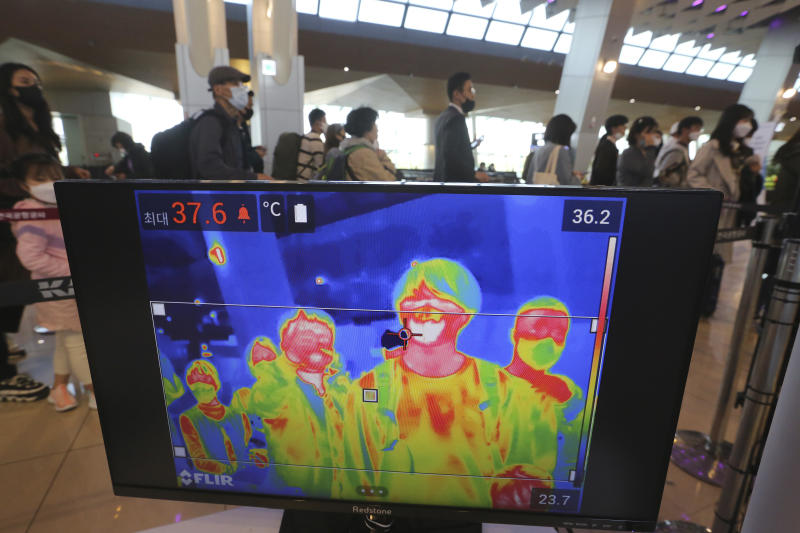 A thermal camera monitor shows the body temperature of passengers as they wait in line before boarding airplanes at the domestic flight terminal of Gimpo airport in Seoul, South Korea, Wednesday, April 29, 2020. South Korean officials have issued public pleas for vigilance to maintain hard-won gains against the coronavirus as the nation enters its longest holiday since infections surged in February. (AP Photo/Ahn Young-joon)