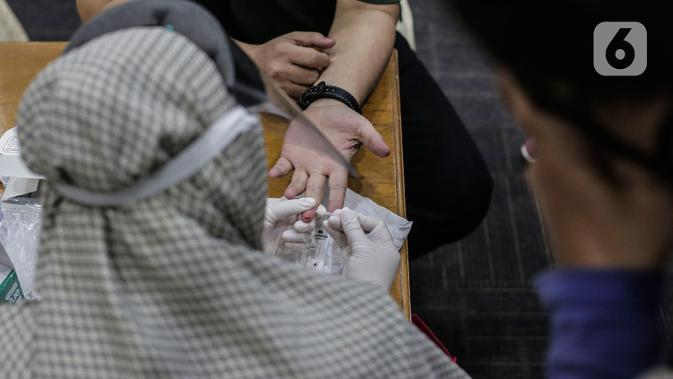 Petugas medis mengambil sampel darah wartawan yang bertugas di DPR saat rapid test di Ruang Wartawan, Kompleks Parlemen, Senayan, Jakarta, Rabu (1/7/2020). Rapid test yang digelar secara gratis ini untuk mendeteksi penyebaran dan memutus mata rantai penularan Covid 19. (Liputan6.com/Johan Tallo)