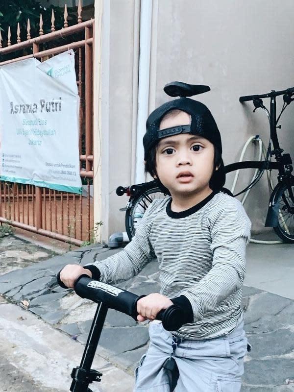 Seperti ayah dan ibunya, Sekala juga memiliki bola mata yang belo. Begini lah ekspresinya saat bermain Scooter. Ia mengenakan topi hitam seperti anak laki-laki yang sudah besar. Menurutmu, Sekala mirip Ayudia atau Ditto? (Instagram/dittopercussion)