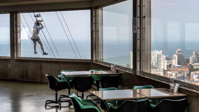 Seorang turis menaiki zipline dari lantai 55 menara observasi Park Beach Resort di Pattaya, Thailand, Rabu (12/2/2020). Pattaya Park Beach Resort adalah salah satu primadona bagi wisatawan China di Pattaya yang kini berangsur sepi karena penyebaran virus corona covid-19. (Mladen ANTONOV / AFP)