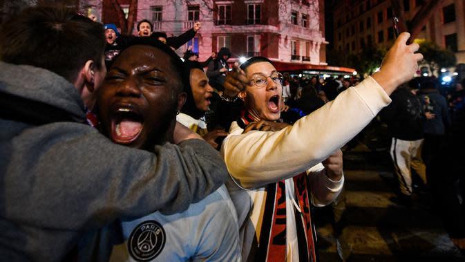 Suporter Paris Saint-Germain (PSG) berpelukan saat merayakan kemenangan PSG atas Borussia Dortmund di depan Stadion Parc des Princes, Paris, Rabu (11/3/2020). Kemenangan tersebut mengantarkan PSG ke perempat final Liga Champions. (AFP/Franck Fife)