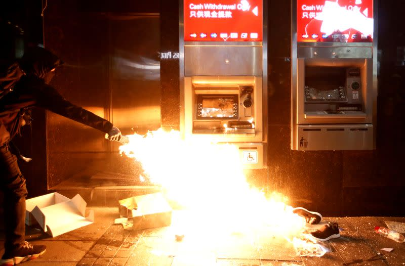 An anti-government protester feeds a flame near an HSBC ATM machine to vandalize it during an anti-government demonstration on New Year's Day to call for better governance and democratic reforms in Hong Kong