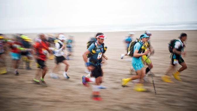 Peserta bersaing pada tahap kedua Half Marathon des Sables di Gurun Ica, Paracas, Peru, Selasa (3/12/2019). Selain kecepatan, para peserta juga diuji ketangguhannya dalam bertahan hidup. (Martin BUREAU/AFP)