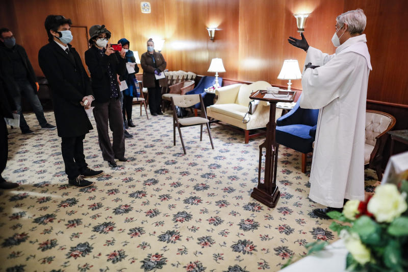 Fabian Arias, a Lutheran pastor with Saint Peter's Church in Manhattan, right, gives a funeral home service besides the casket of Hector Cabana who died of COVID-19, Monday, May 11, 2020, in the Brooklyn borough of New York. (AP Photo/John Minchillo)
