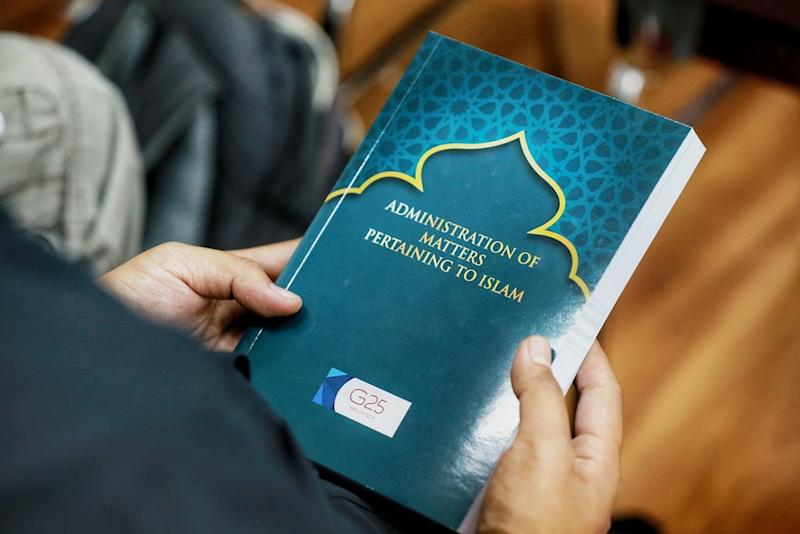 A man holds a copy of G25's 'Administration of Matters Pertaining to Islam' report in Kuala Lumpur January 11, 2020. — Picture by Ahmad Zamzahuri