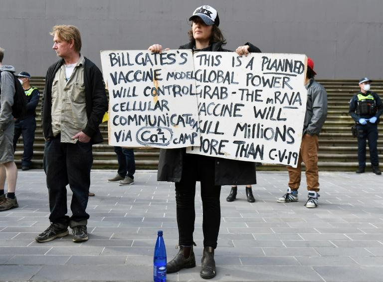 An anti-lockdown protester holds placards on the steps of Victoria's state parliament in Melbourne