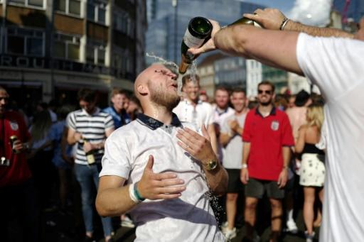 A man is drenched in champagne in a London street as England fans celebrate