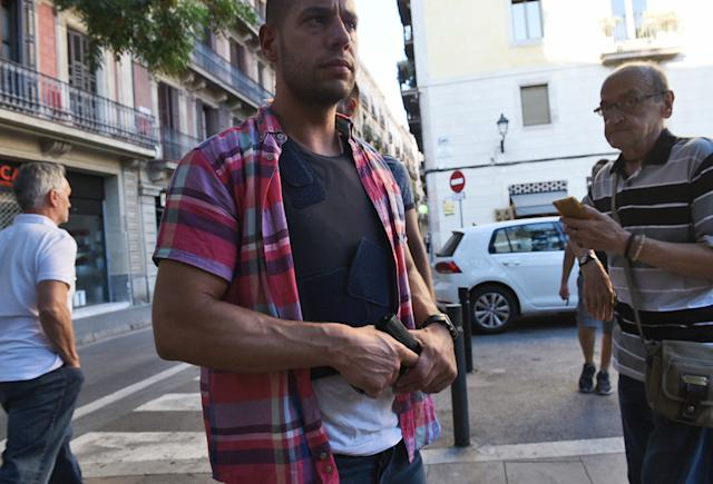 A plain clothed police officer secures the area in Barcelona. (AP Photo/Giannis Papanikos)