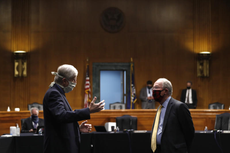 """FILE - In this Thursday, May 7, 2020 file photo, National Institutes of Health Director Dr. Francis Collins, left, speaks with Chairman Sen. Lamar Alexander, R-Tenn., prior to a Senate Health Education Labor and Pensions Committee hearing on new coronavirus tests on Capitol Hill in Washington.  Collins has lauded the majority of American faith communities for treating the pandemic as an opportunity to live out their values by helping the vulnerable. He also offered careful criticism for the """"occasional examples of churches who reject the scientific conclusions and demand the right to continue to assemble freely, even in the face of evidence that this endangers their whole community.""""(AP Photo/Andrew Harnik, Pool)"""