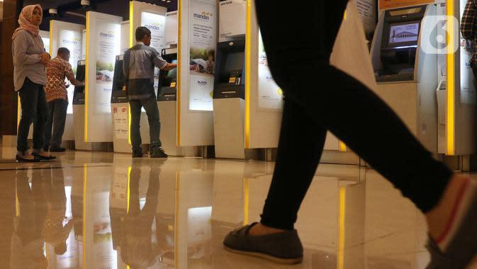 Nasabah melakukan transaksi elektronik perbankan melalui ATM di Jakarta, Selasa (4/2/2020). Transaksi kanal elektronik Bank Mandiri sepanjang 2019 juga terdongkrak naik empat persen secara yoy menjadi Rp 2,1 miliar transaksi dengan nilai finansial sebesar Rp 3,1 triliun. (Liputan6.com/Angga Yuniar)
