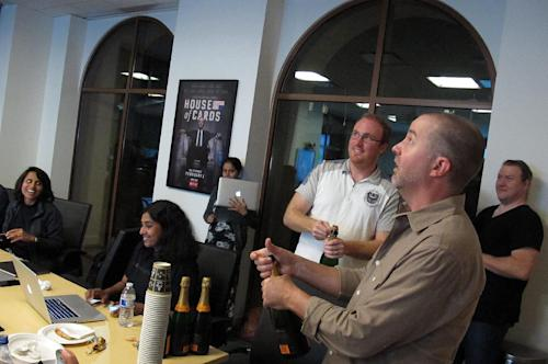 "In this Thursday, July 11, 2013, photo, Chris Jaffee, Netflix VP of Product Innovation, pops the cork on a champagne bottle after the debut of the new series ""Orange is the new black"" in Los Gatos, Calif. (AP Photo/Michael Liedtke)"