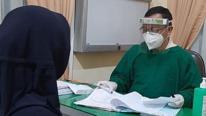 Seorang petugas medis sedang melayani warga di klinik Covid-19 RSUD Raden Mattaher Jambi, (26/3/2020). Klinik ini dibuka untuk pencegahan, terutama bagi warga yang baru pulang dari luar daerah. (Liputan6.com / Humas Prov/ Gresi Plasmanto)