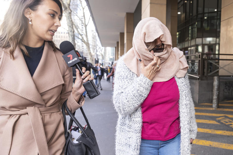 Rosanna Ashman (right) leaves the Melbourne Magistrates Court with her face covered.