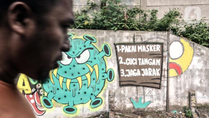 Warga melintasi mural bertema imbauan protokol kesehatan COVID-19 di kawasan Cakung Barat, Jakarta, Minggu (18/10/2020). Mural karya warga setempat tersebut bertujuan mengingatkan masyarakat akan pentingnya memakai masker, menjaga jarak, dan mencuci tangan. (merdeka.com/Iqbal S. Nugroho)