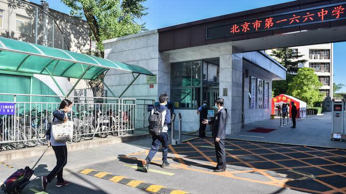 Para siswa memasuki gedung Sekolah Menengah No. 166 di Beijing, ibu kota China, (11/5/2020). Beijing pada Senin (11/5) memulai kembali kegiatan belajar di kelas untuk siswa tingkat akhir di seluruh sekolah menengah pertama seiring meredanya dampak COVID-19. (Xinhua/Peng Ziyang)