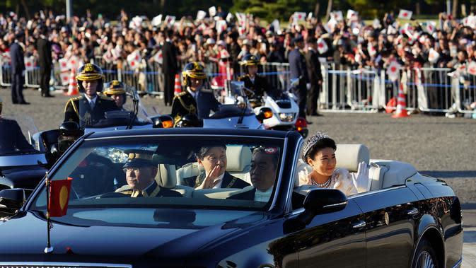 Kaisar Jepang, Naruhito dan Permaisuri Masako menyapa warganya selama parade di Tokyo, Jepang, Minggu (10/11/2019). Parade digelar dalam rangka mengakhiri serangkaian acara penobatan Kaisar Naruhito sejak 1 Mei 2019, atau sehari setelah Akihito turun takhta. (AP Photo/Eugene Hoshiko)