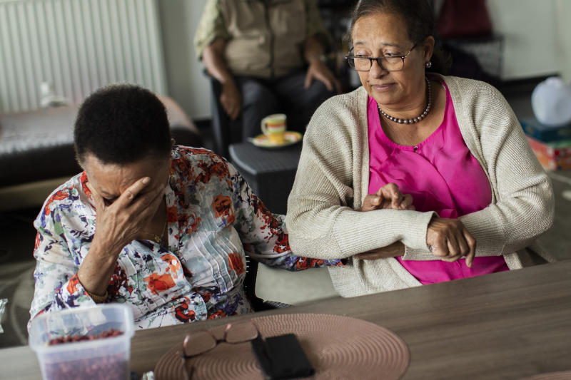 In this photo taken on Monday, June 29, 2020, Marie-Jose Loshi, left, cries as she is comforted by her friend Monique Bitu Bingi during an interview with The Associated Press in Brussels. Loshi and Bingi are part of a group of biracial women who were taken from their families as children in Belgian Congo and placed in a religious mission run by Catholic nuns who have now filed a lawsuit seeking reparations from Belgium. (AP Photo/Francisco Seco)
