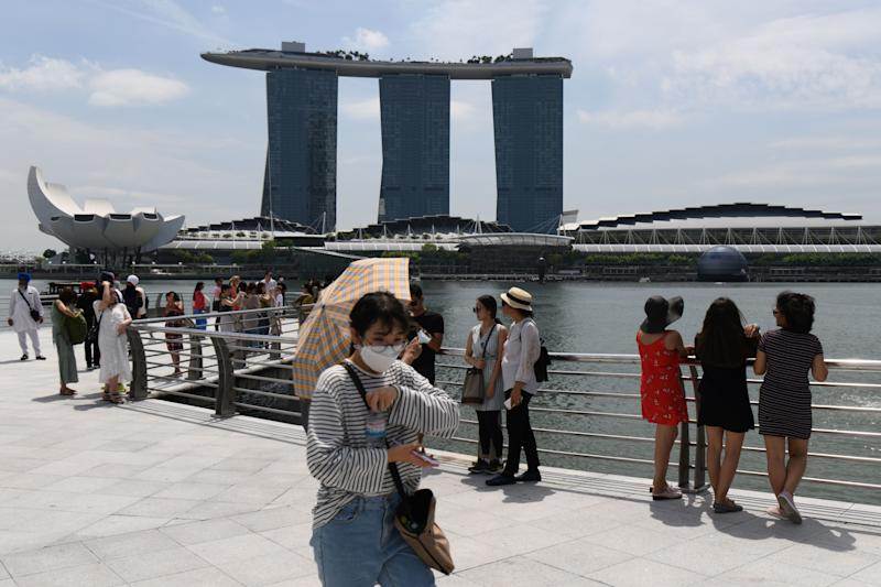 A visitor, wearing a protective facemask amid fears about the spread of the COVID-19 novel coronavirus, walks along Merlion Park. (PHOTO: AFP via Getty Images)