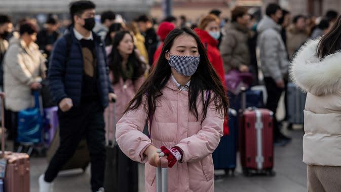 Orang-orang mengenakan masker penutup mulut setibanya di stasiun kereta api Beijing untuk mudik Tahun Baru Imlek pada Selasa (21/1/2020). Virus mirip SARS yang menyebar ke seluruh wilayah China dan mencapai tiga negara Asia ternyata dapat menular dari satu orang ke orang lain. (NICOLAS ASFOURI/AFP)